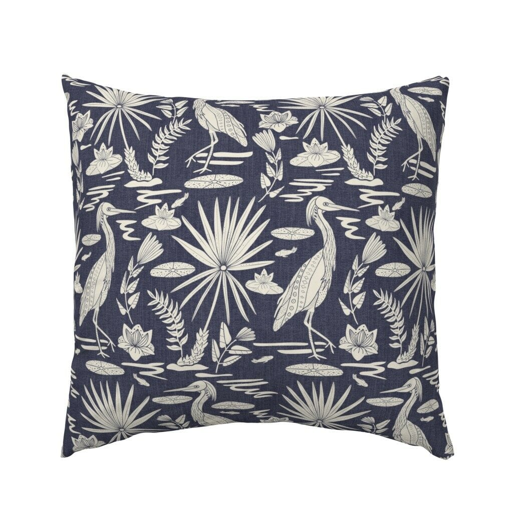 Square pillow with black and white Egrets and foliage on a blue background