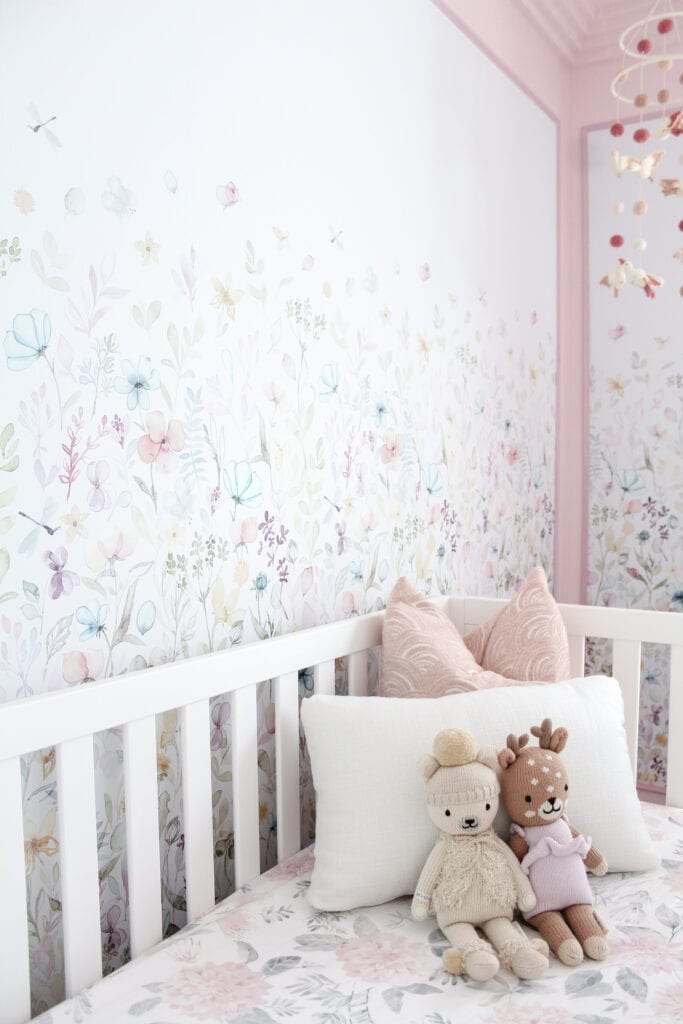 A children's bed with pillows and stuffed animals next to a wall featuring pastel floral illustrations