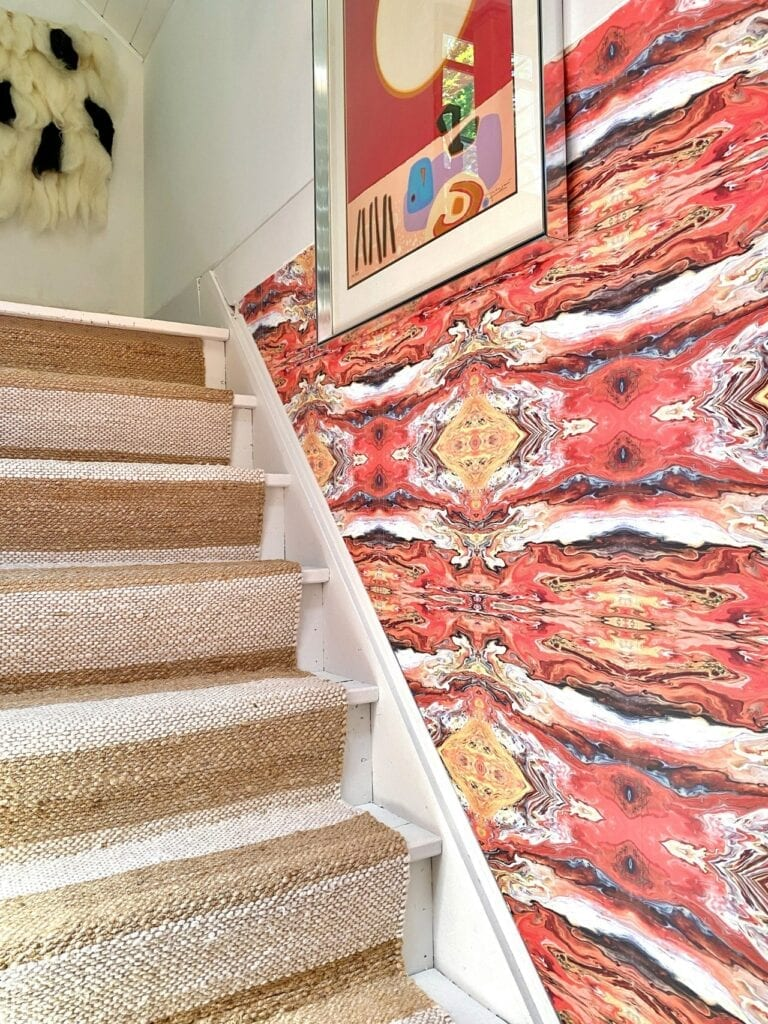A stairway with a wall featuring a symmetrical red abstract design