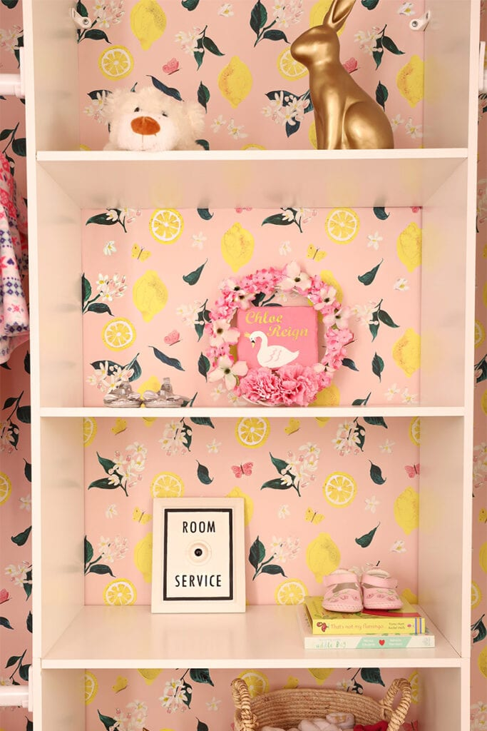 A closet shelf with children's book, shoes, and toys features a lemon wallpaper on the back