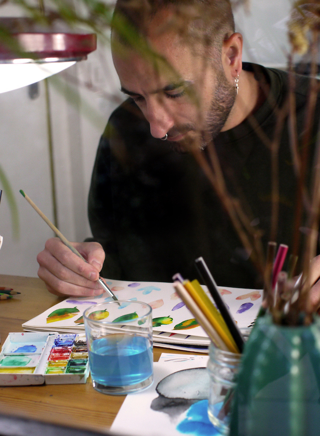 Artist works in sketchbook drawing leaves and flowers with watercolors
