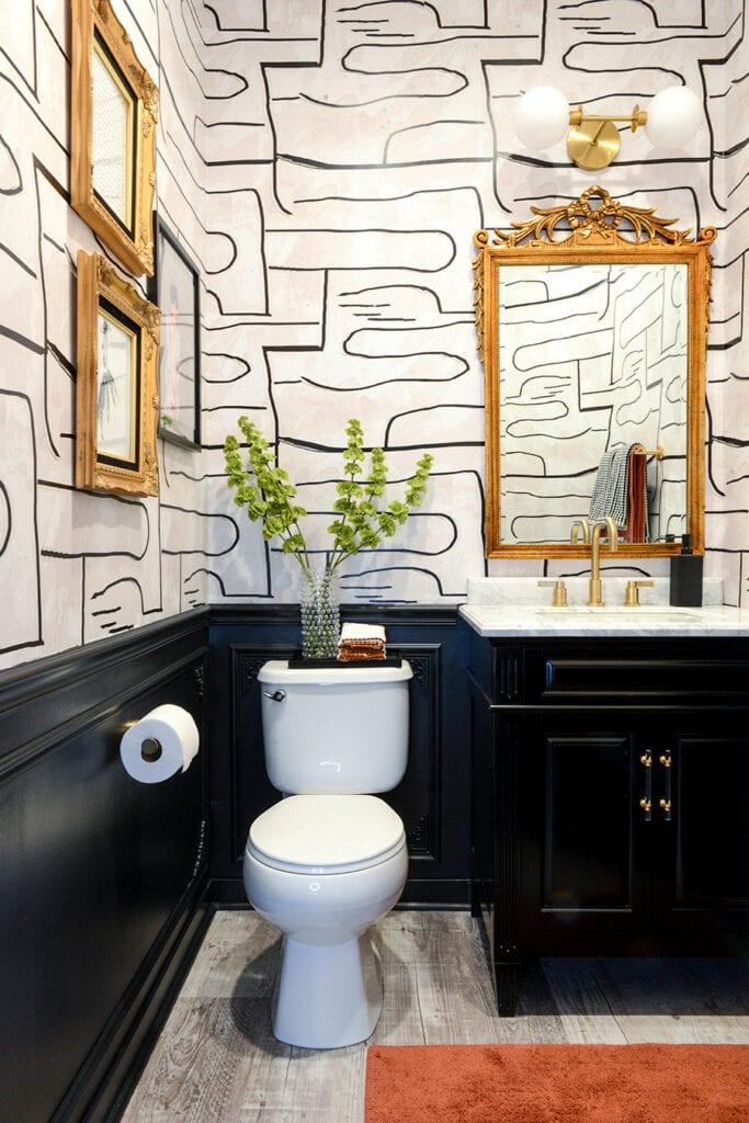 A bathroom features an abstract black and white designed wallpaper