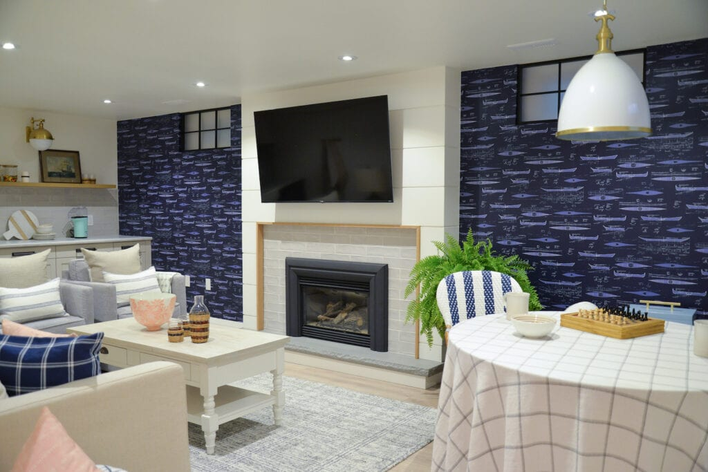 A Living room with couch, television, and fireplace features a wallpaper featuring a blue print design