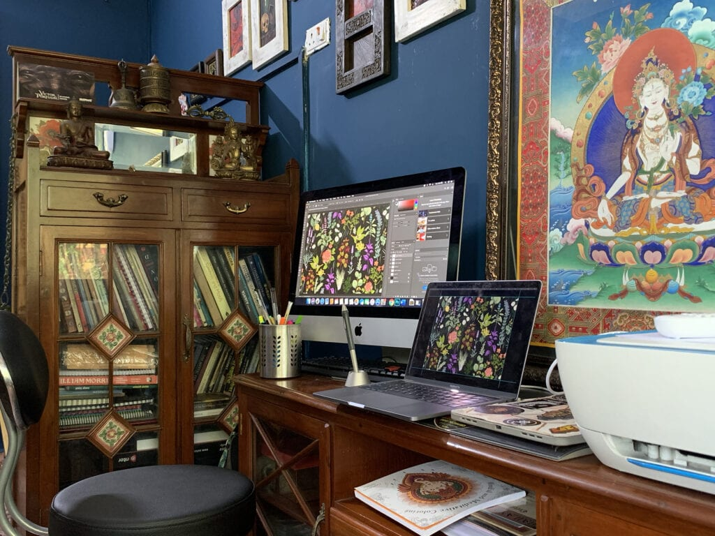 Desk with laptop and monitor showing a colorful design in progress