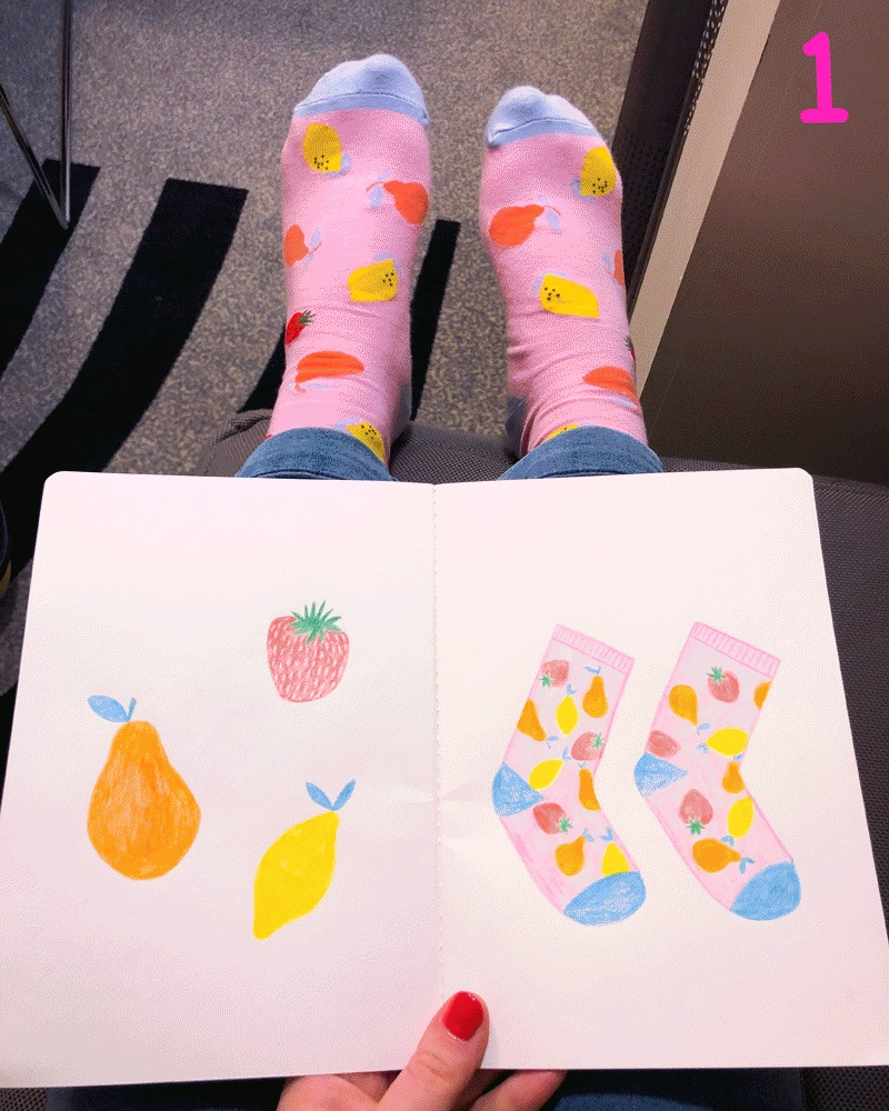 A sketchbook on top of legs with feet wearing pink socks with fruit on them. The sketchbook has a drawing of the socks.