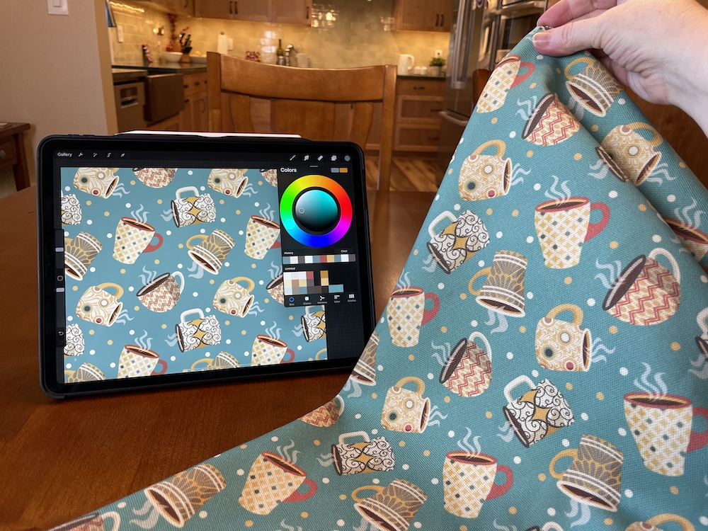 A hand holds a teal fabric with printed coffee mugs in front of an IPad showing the same design.