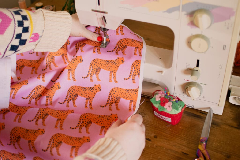 Two hands sewing pink fabric with orange tigers on it on a sewing machine.