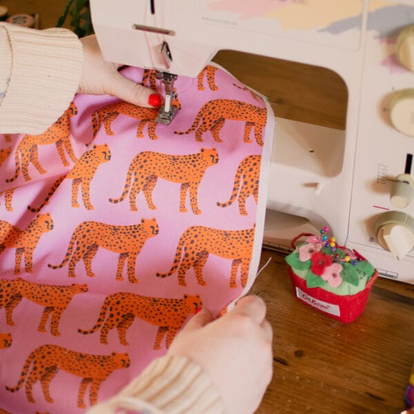 Fabric with orange tigers and a pink background being sewn on a sewing machine.
