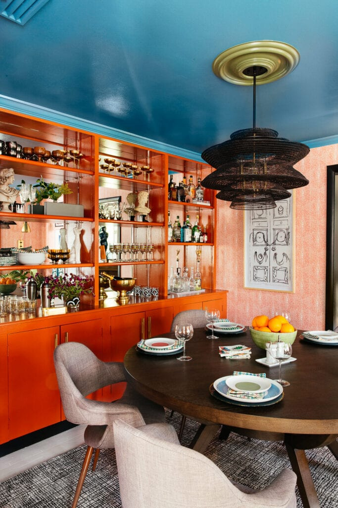 A dining room with orange built in shelving, orange patterned wallpaper, and a bright blue ceiling.