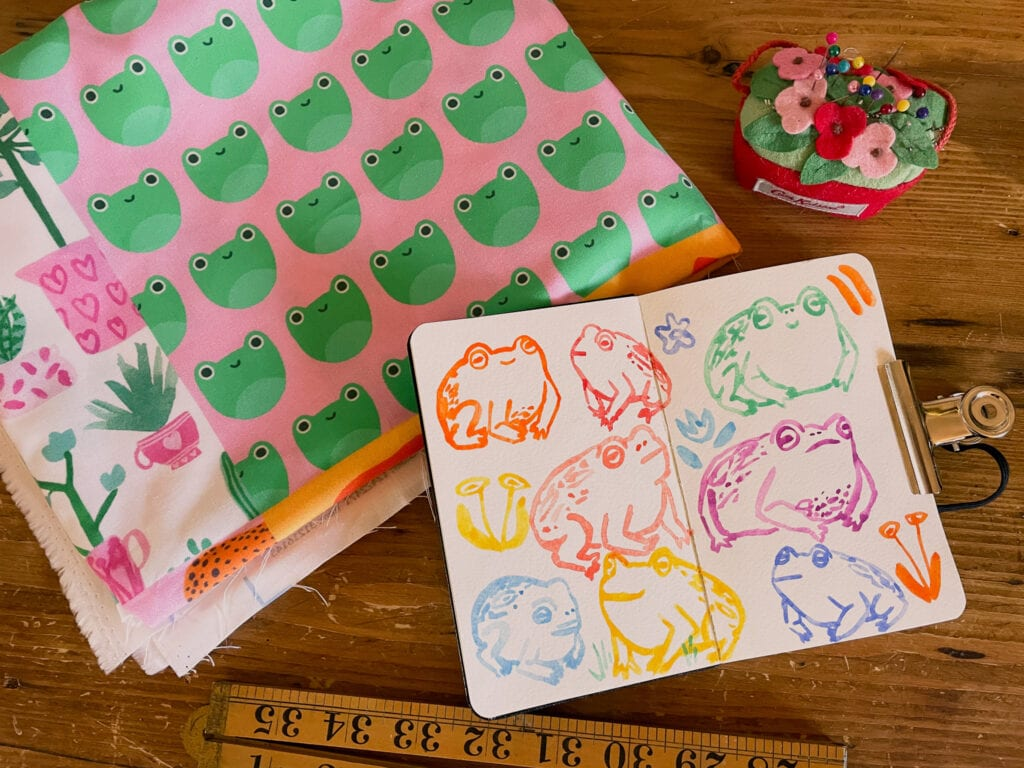 A sketchbook of illustrated multi-color watercolor frogs sits next to a fabric stack featuring a a design