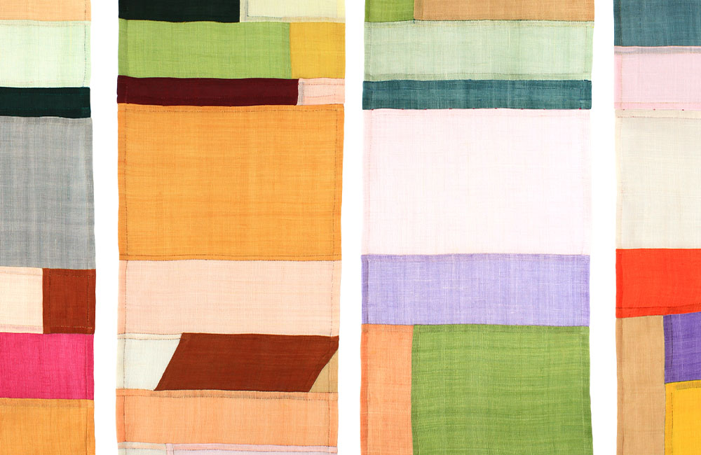 Colorful patches of fabric sewn together into four strips