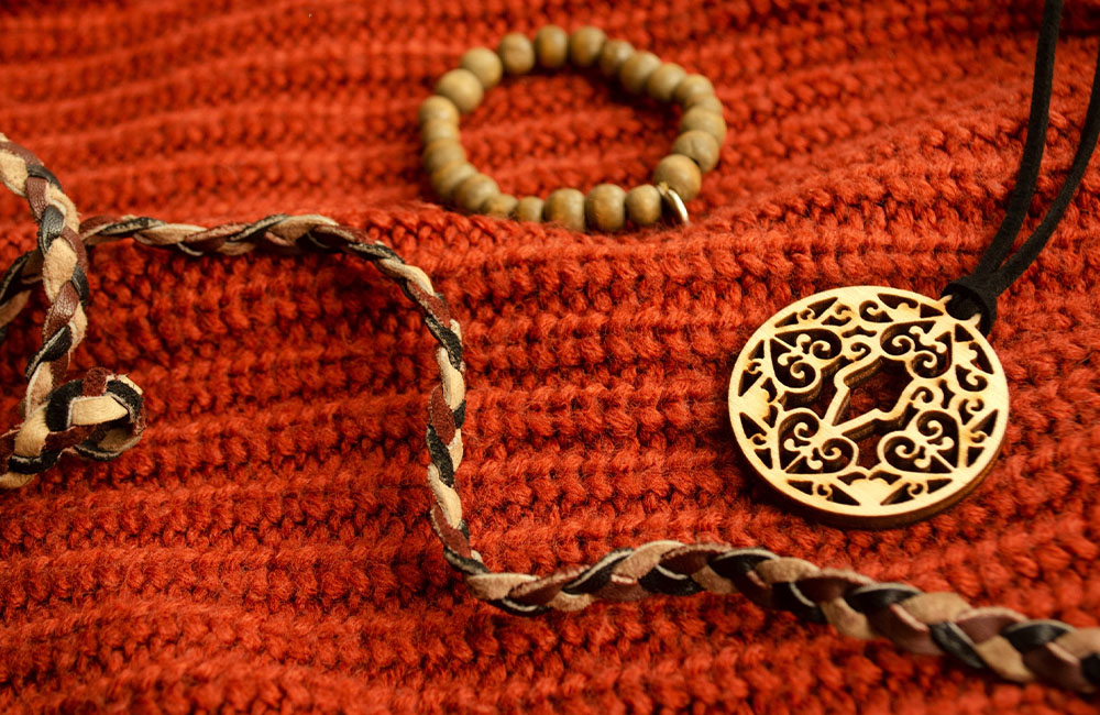 A brown beaded bracelet, a golden charm on a necklace and a braided leather strap sit on an orange knitted background