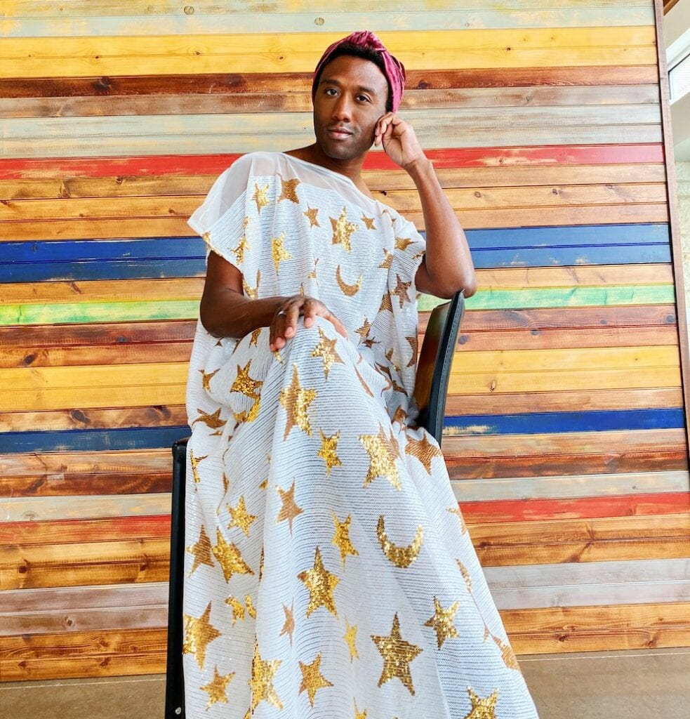 Terrance Williams sits in front of a colorful wood wall wearing a handmade headband and white caftan dress with a gold stars and moons pattern
