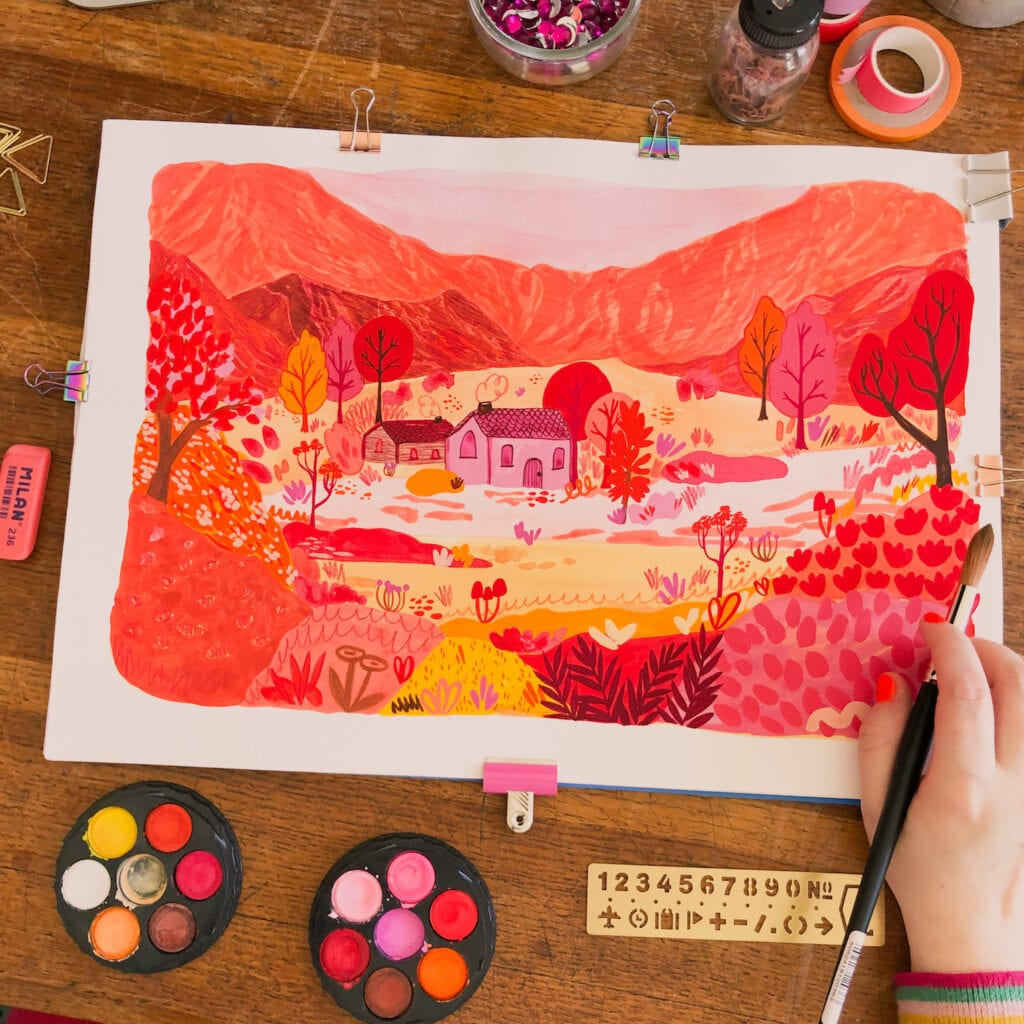 An artist's hand with a paintbrush working on a illustration of a landscape with two tiny houses, mountains, trees and flowers using pinks, red, yellows and oranges