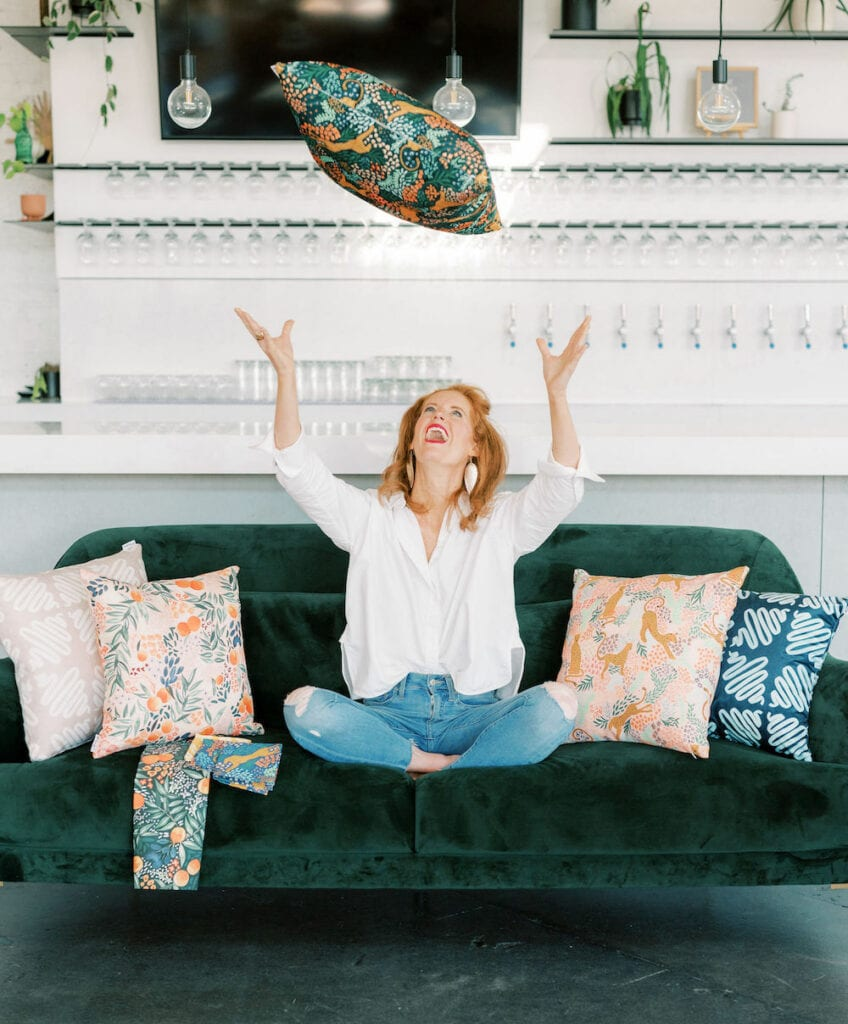 Em on a couch with a collection of pillows designed by Alison.