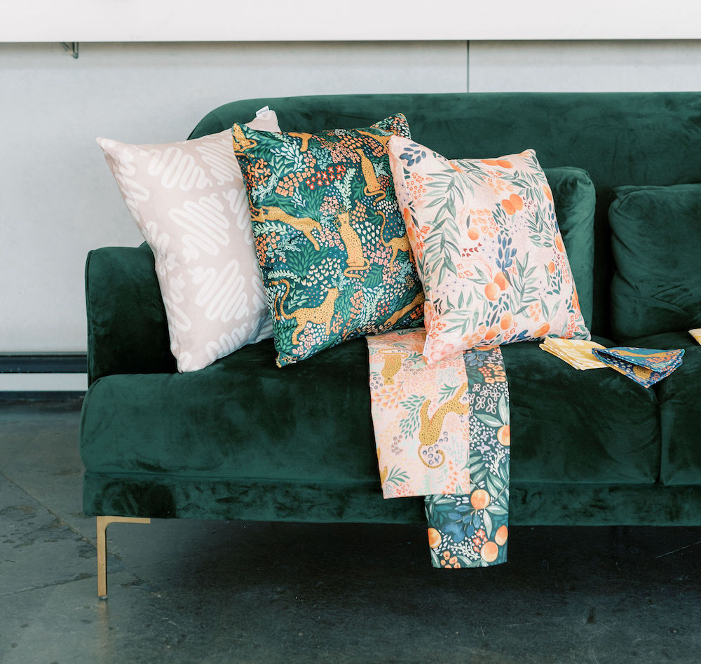 Pillows, napkins, and tea towels designed by Alison on a green couch