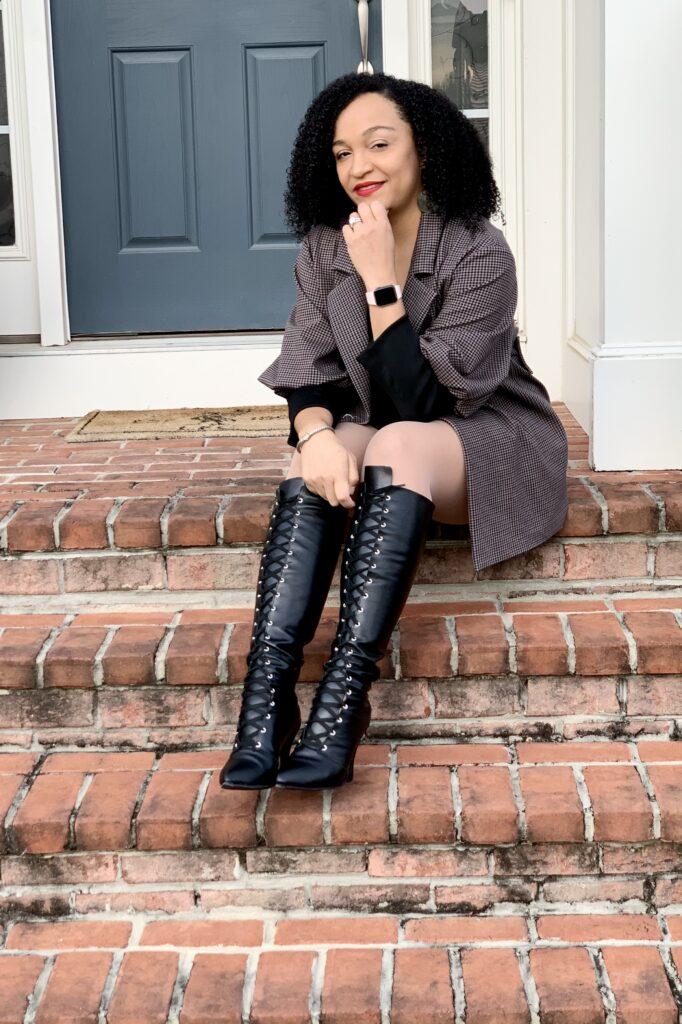 Jaimie sitting on porch stairs with grey outfit and black boots