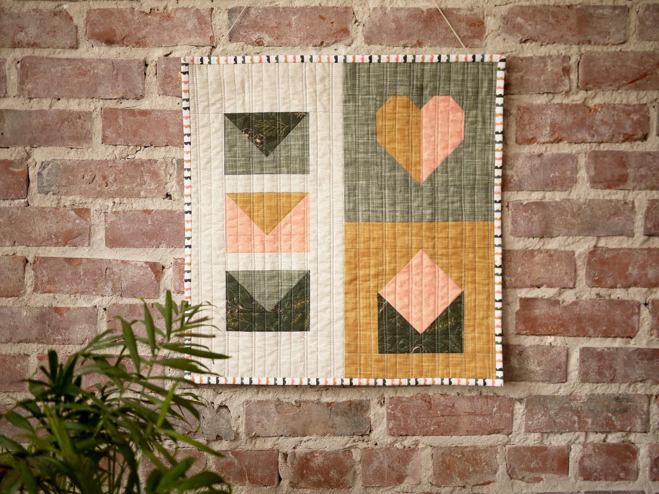 Finished quilt blocks hanging on a brick wall