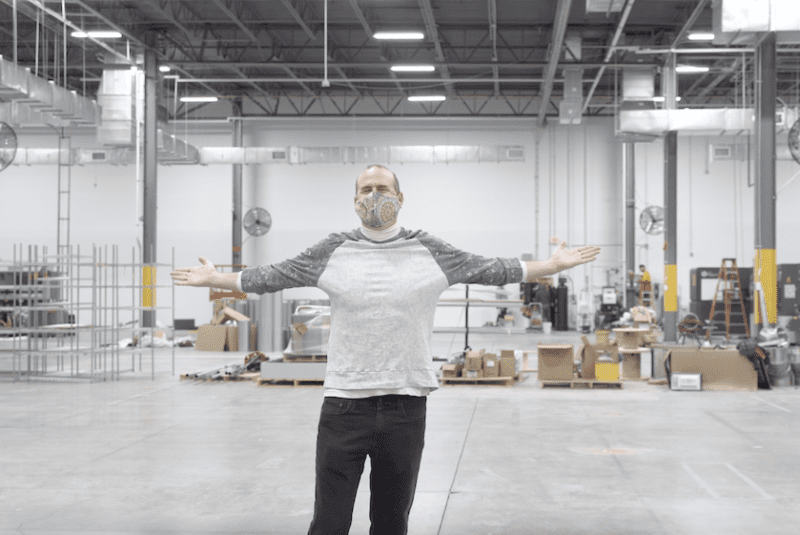 Gart stands in a large factory space with his arms outstretched