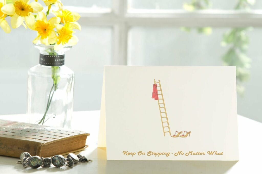 Greeting card sitting on a table with a vase of flowers