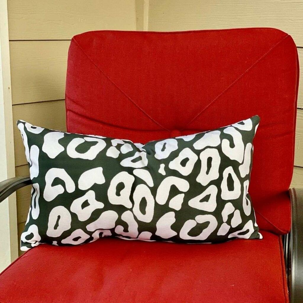 Ein schwarz weißes Leopardenkissen aus Recyceltem Canvas auf einem roten Sessel