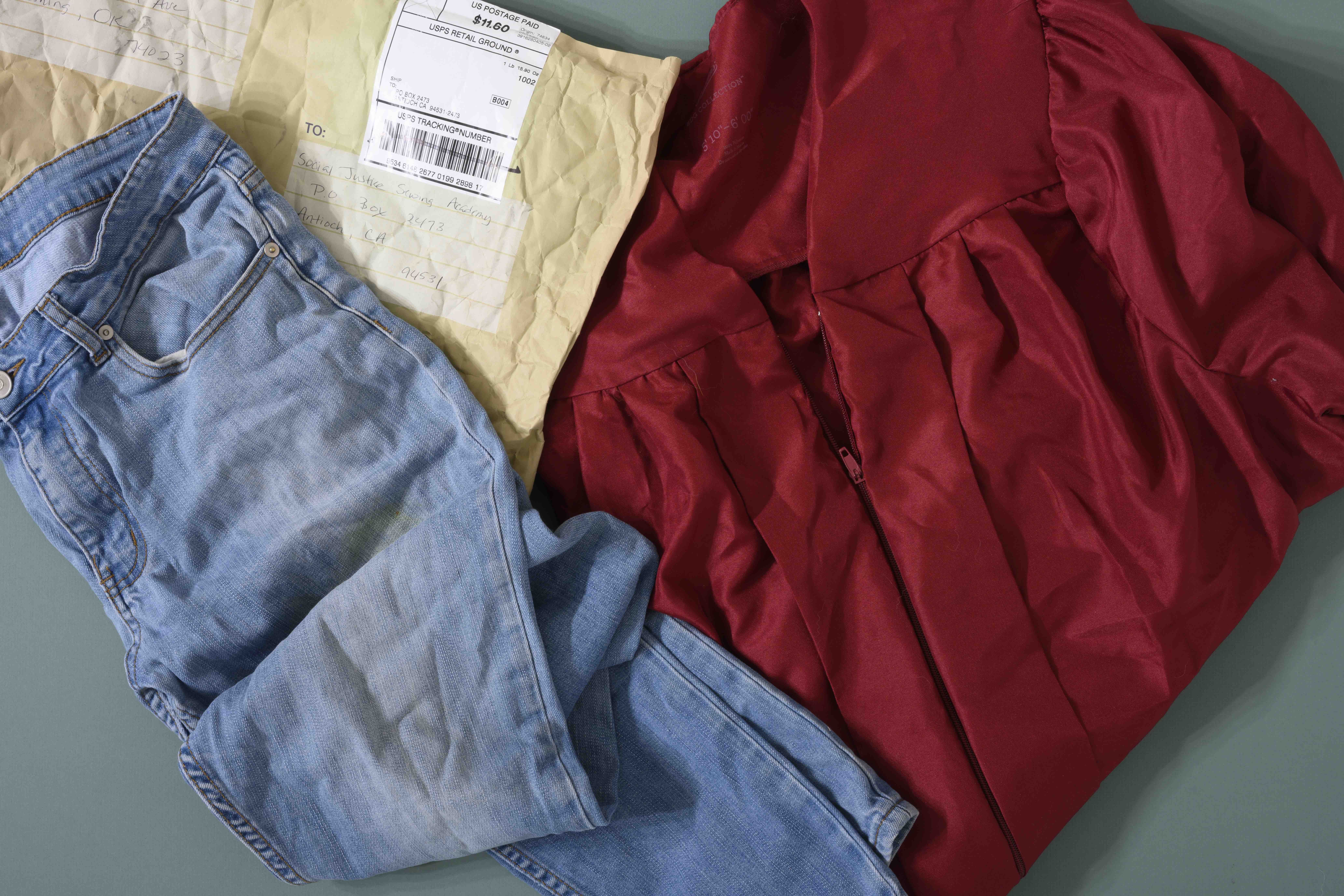 An old mailer, graduation robe, and pair of jeans