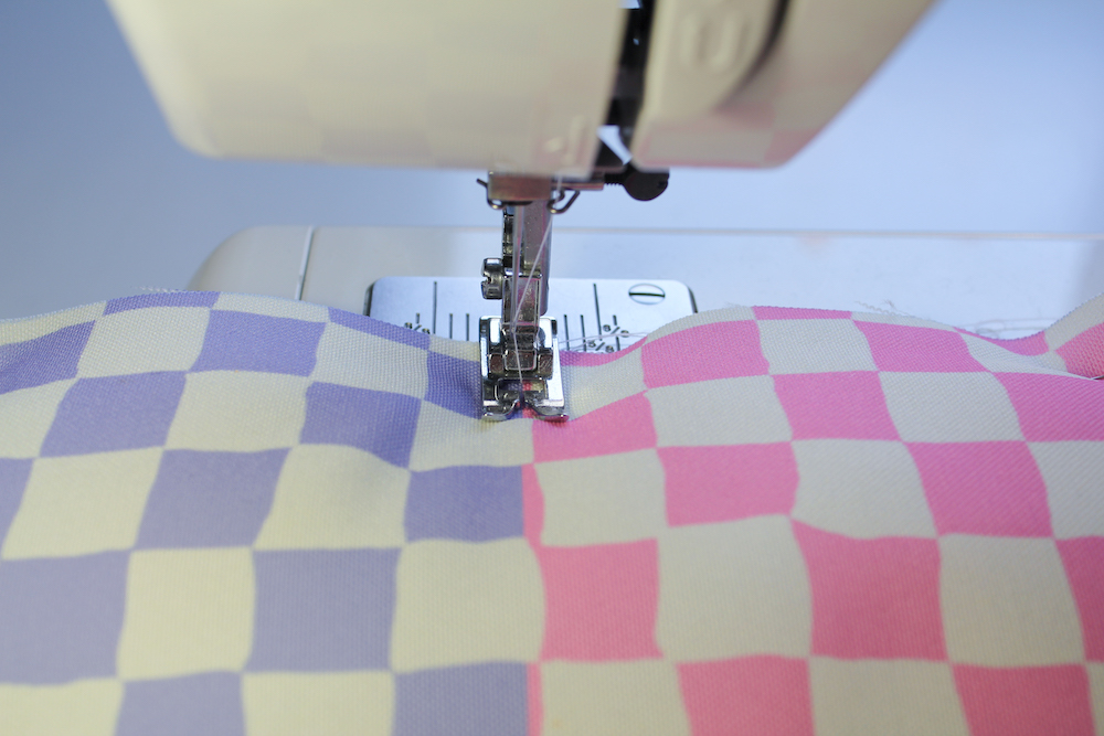 Sewing machine quilting the top layer of fabric