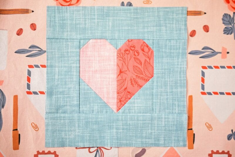A quilt block with a heart on top of a fabric design with envelopes, stamps and writing utensils