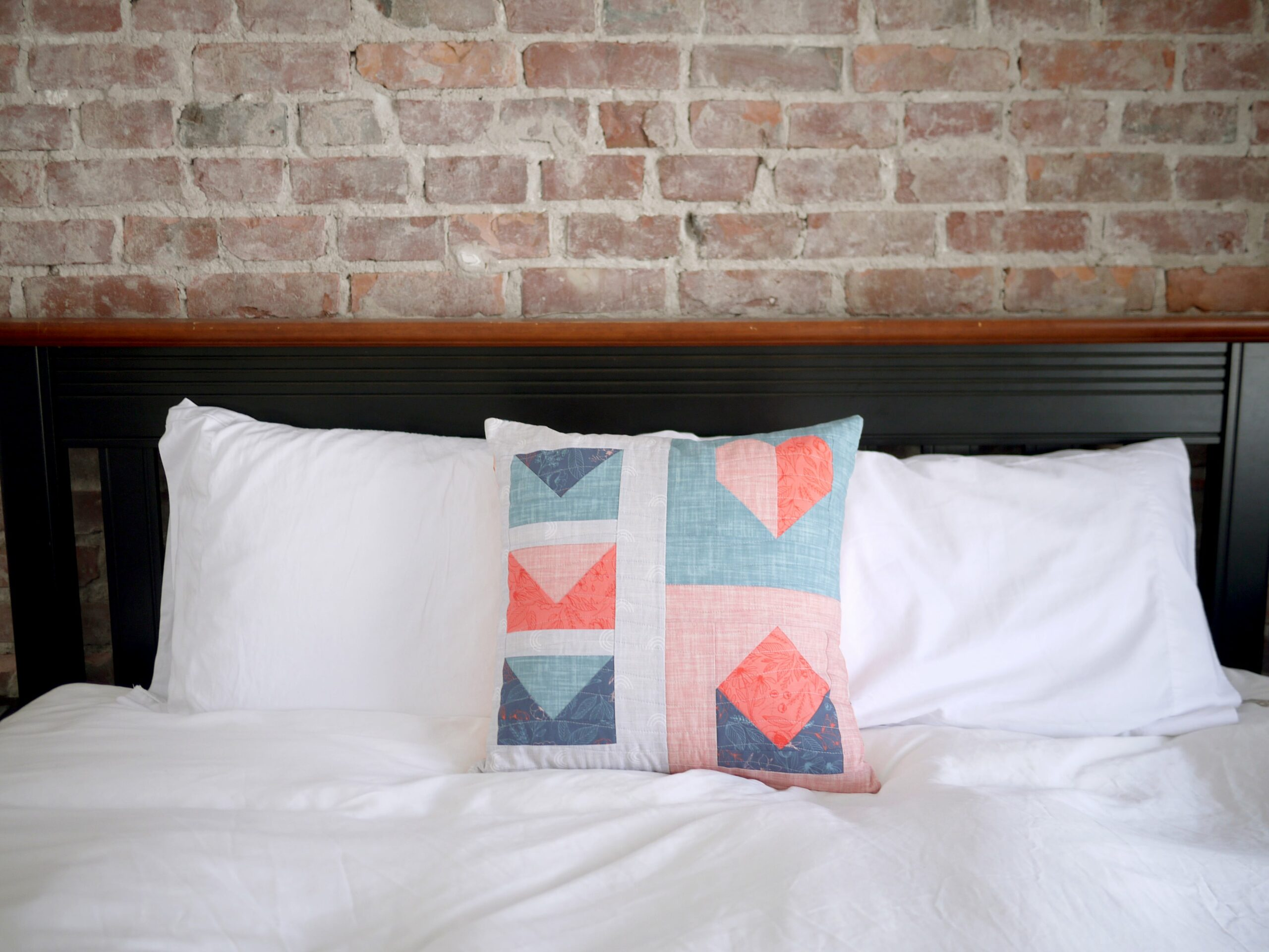 Pillow made with quilt blocks sitting on bed