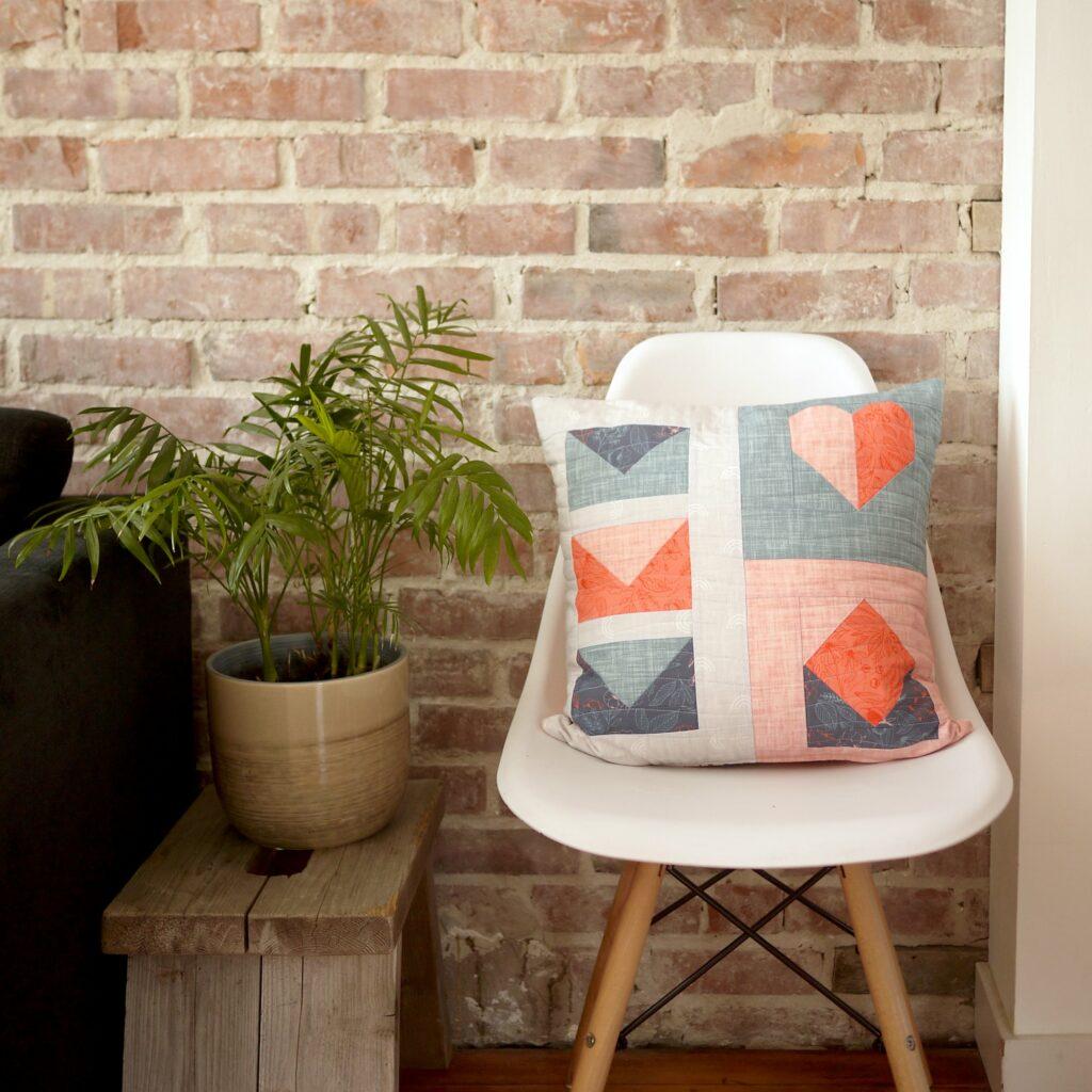 Dass fertige Quilt unserer Quilt Quadrat Party als Zierkissen auf einem Stuhl