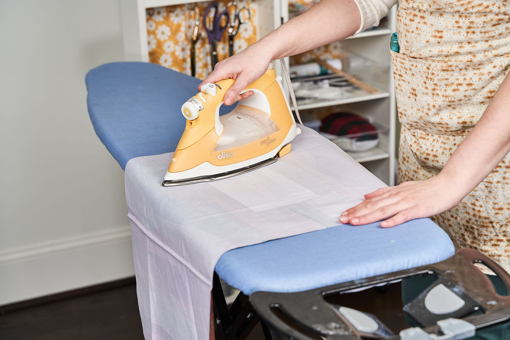 Ace irons the fusing on the fabric