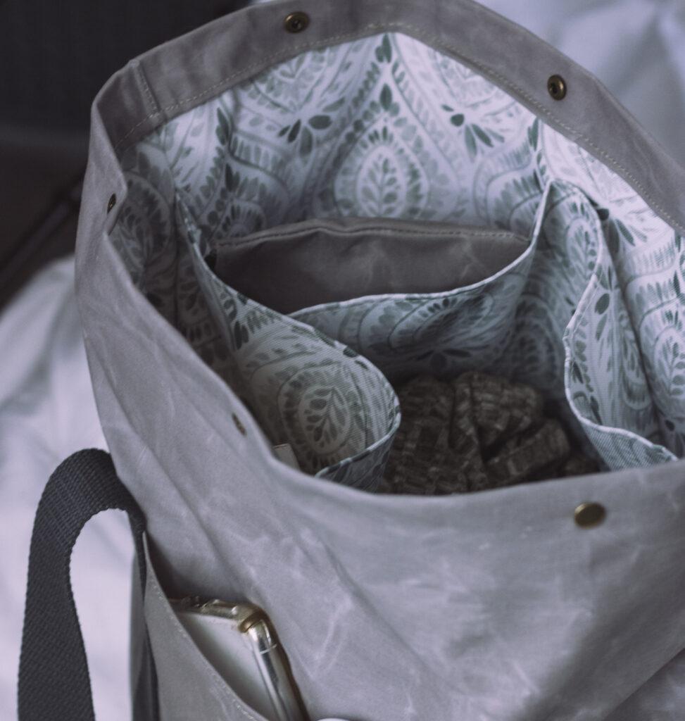 Ein grauer Rucksack mit Blätterdesign als Futter aus Recyceltem Canvas