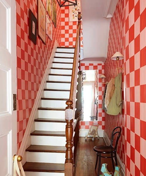 An entryway with pink and red checker wallpaper