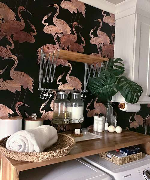 A laundry room with a wallpaper featuring pink birds on a black background