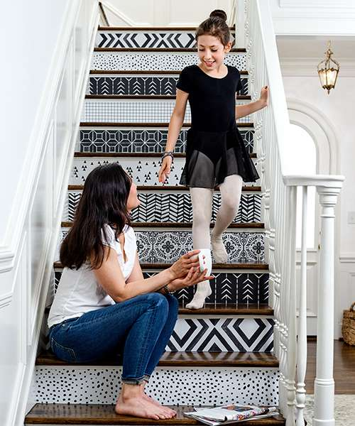 A girl walks down stair with a different black and white designs on each step
