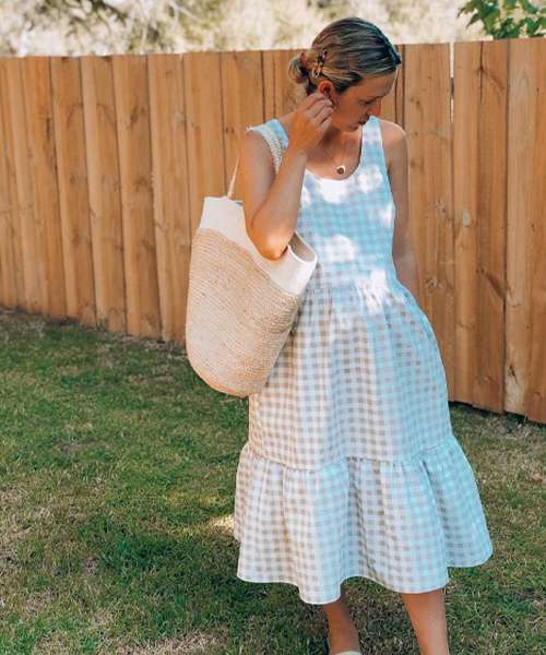 A women wearing a beige and white gingham dress