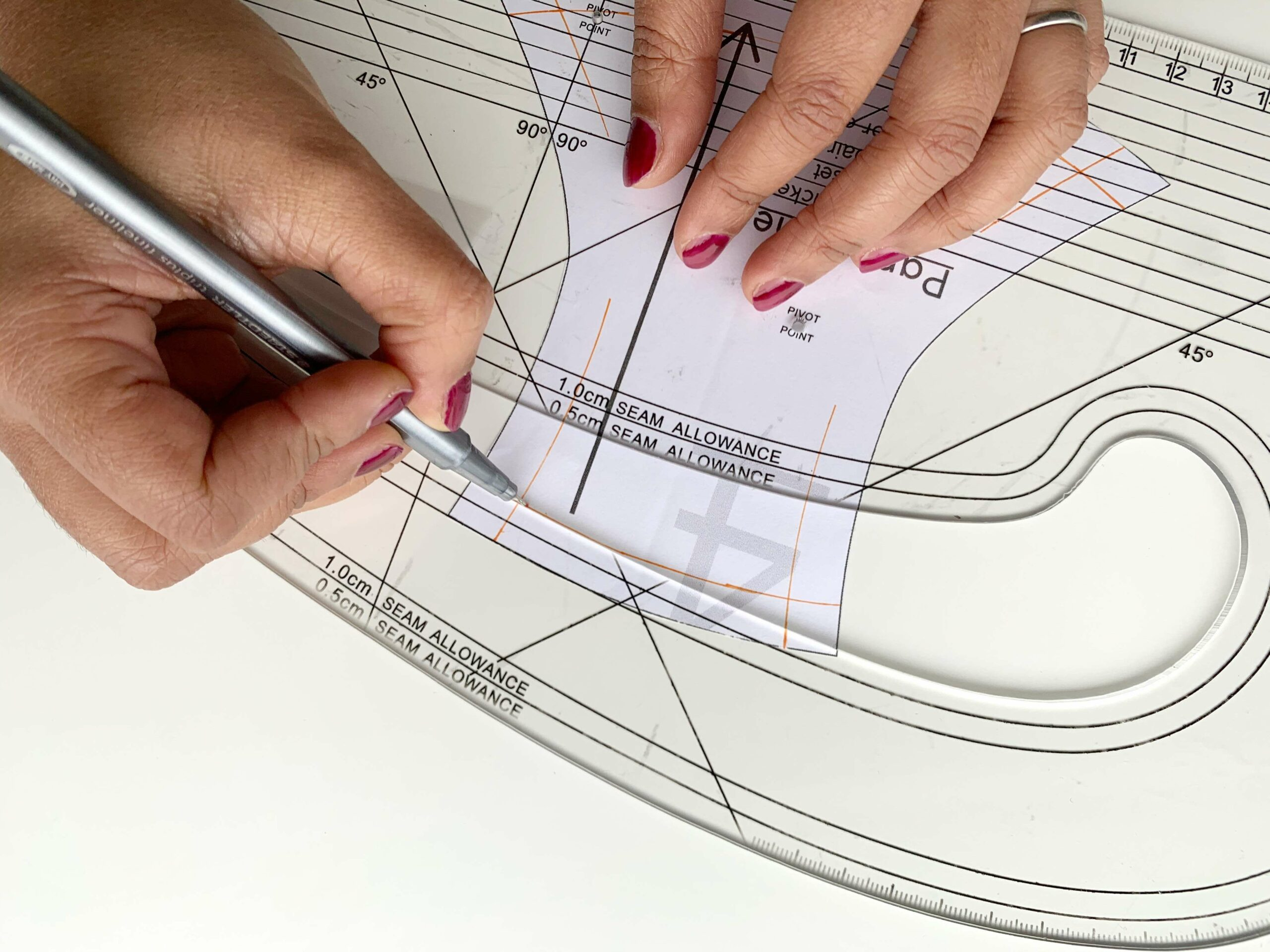Drafting the new underwear pattern by marking stitch lines on the paper