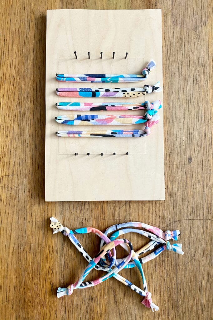 Five fabric strips stretched across wooden loom
