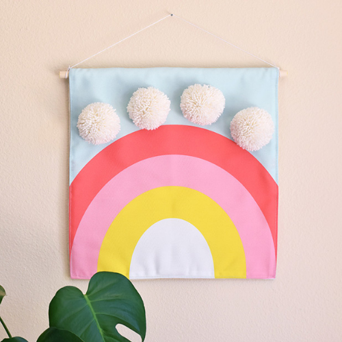 A wall hanging featuring a rainbow with pom poms