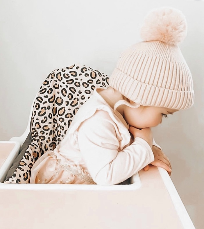A child sits in a high chair featuring a cover from Yeah Baby Goods