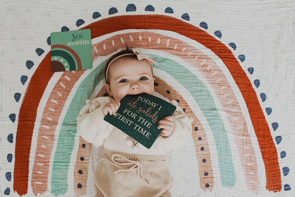 Ein Produktbild eines Babys auf einer Regenbogendecke von Katie für Etsy (nach der Bildbearbeitung)