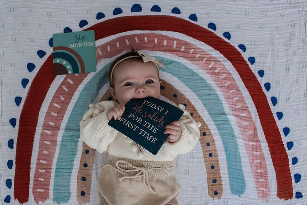 Ein Produktbild eines Babys auf einer Regenbogendecke von Katie für Etsy (vor der Bildbearbeitung)
