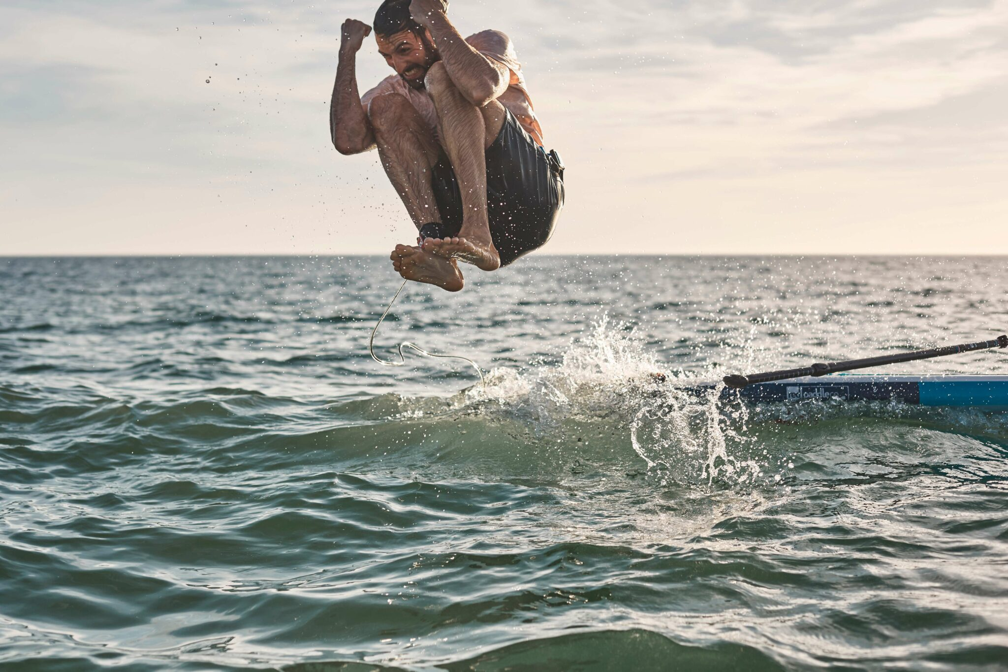 Person jumping into the ocean from their paddle board