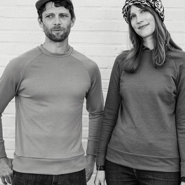 Two people wearing pullover sweatshirts