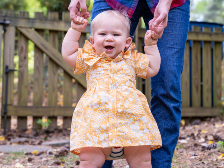 Baby with yellow ruffled dress