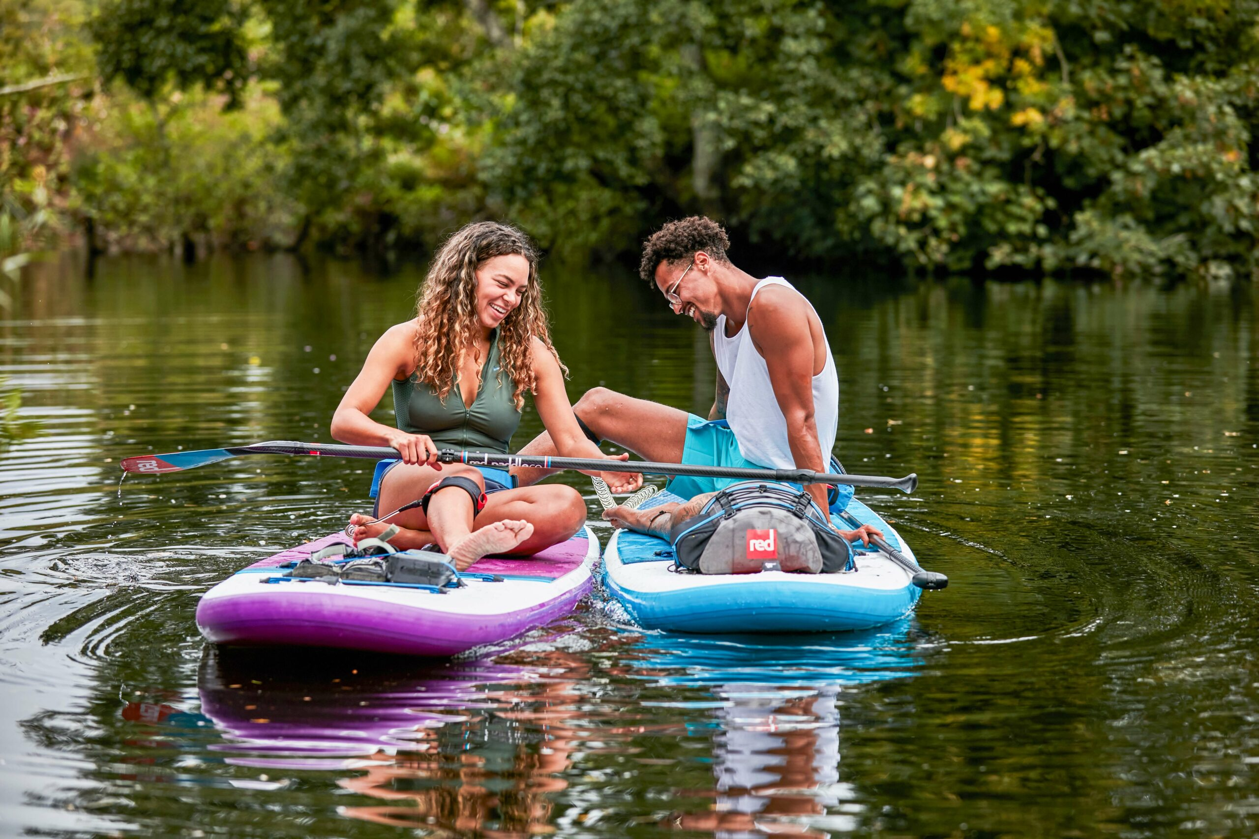 Two people sitting on paddle boards in a lake