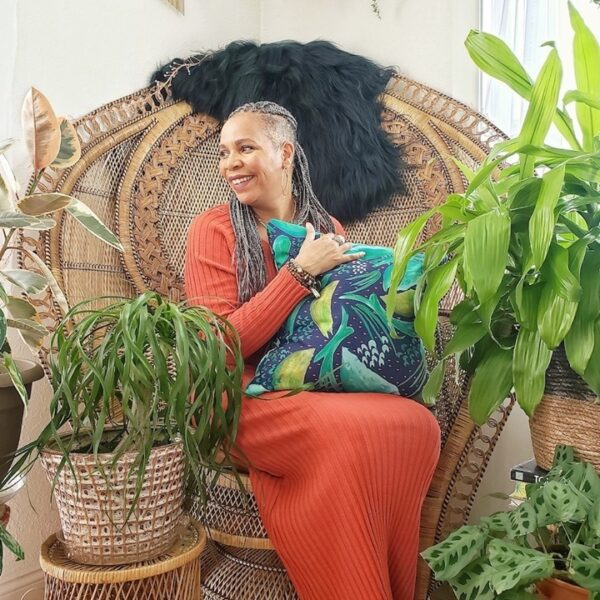 Tracey Hairston sits in a chair holding a pillow and surrounded by plants