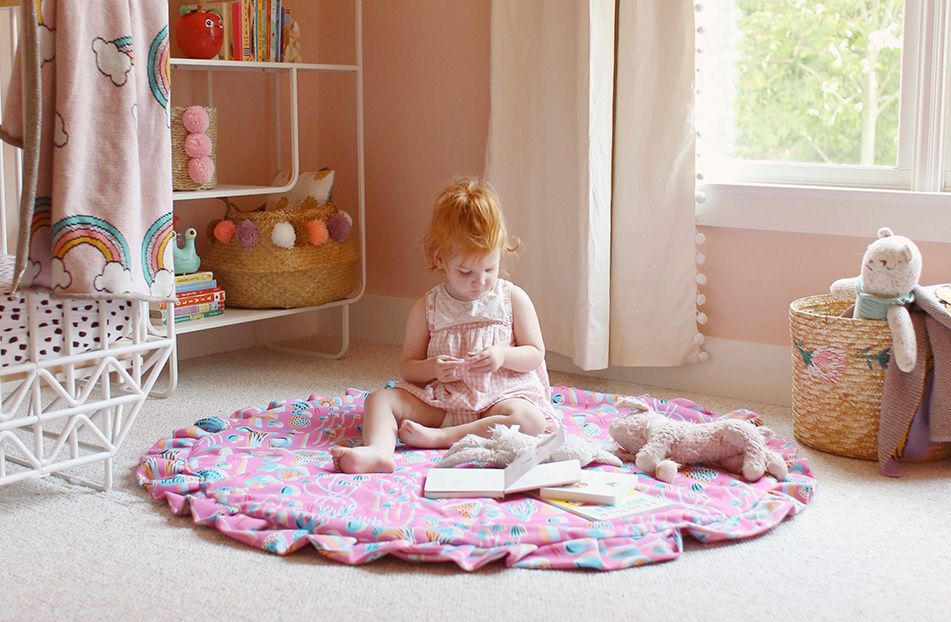 Toddler sitting on a pink playmat in playroom