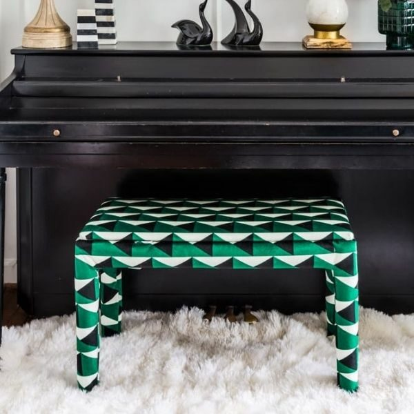 Upholstered green, black, and white piano bench