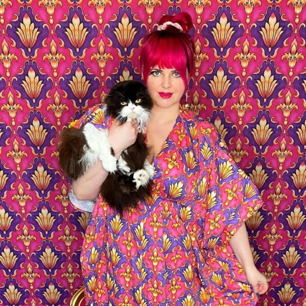 Women in a patterned dress stand in front of a wallpaper wall with the same pattern while holding a cat wearing the same pattern